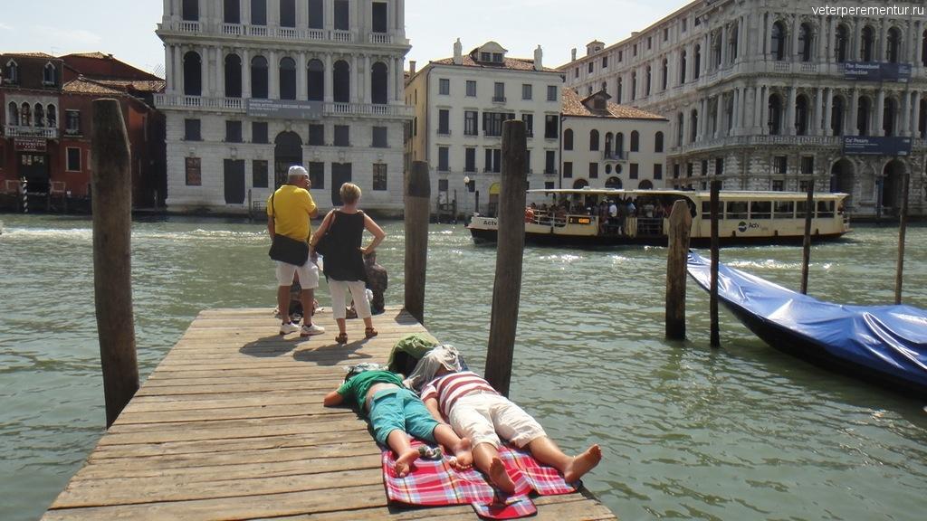 Туристы отдыхают на мостках канала в Венеции