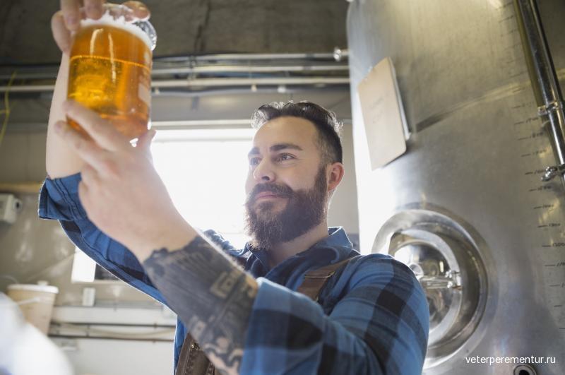 brewery-worker-examining-beer-in-beaker